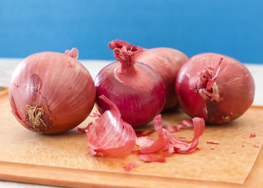 red onion on cutting board with some peels broken off